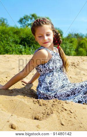 Portrait of pretty girl sitting on sand