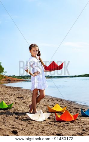 Cute little girl posing with colorful paper boats