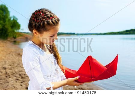 Image of lovely girl with red paper boat