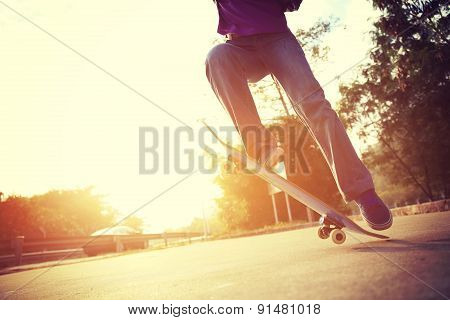 young skateboarder doing a skateboarding trick ollie at sunrise