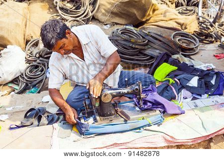 Orissa, India - Nov 10 - Indian Men Tailors Run Their Sewing Machines In The Shade At The Weekly Mar