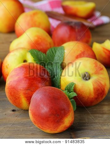 ripe organic peaches with mint leaves on a wooden table