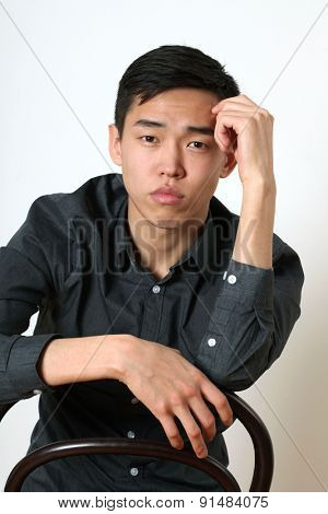 Romantic young Asian man sitting on a chair and looking at camera.