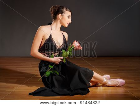 Young ballerina with flower on the floor