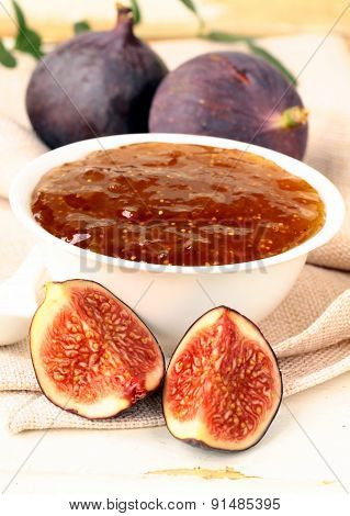ripe purple figs jam  in a white bowl with fresh fruit