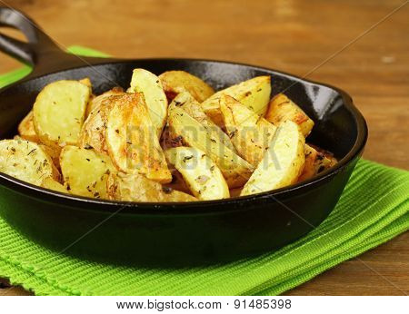 slices of fried potatoes with spices in a cast iron pan