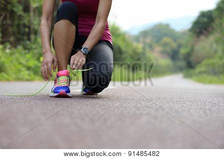 young asian woman tying shoelace on fossil forest trail
