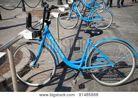 Modern Blue City Bicycles For Rent Stand On A Parking