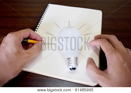 man hand drawing a light bulb on note paper (idea concept)