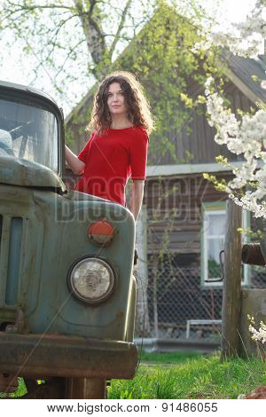 Standing on running board of old truck brunette girl in red dress