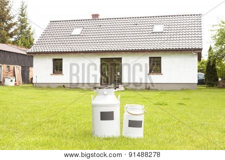 Milk Cans In Front Of A House.