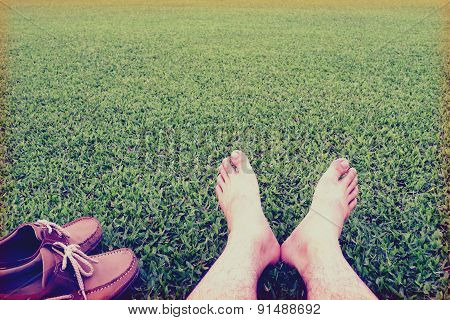 Men's feet ans shoes on the background of lush green grass ,vintage style