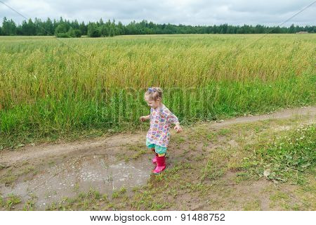Blonde curly preschooler girl playing on farm dirt road near puddle
