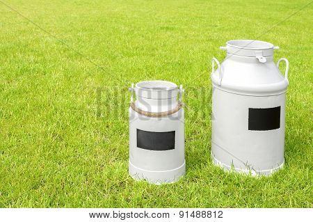 Retro Milk Cans On A Green Grass.