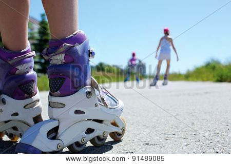 Children Ride On Roller Skates In The Park On A Warm Summer Day