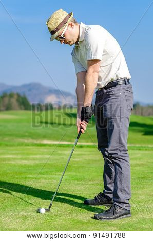 Golfer Is Chipping A Golf Ball Onto The Green With Driver Golf Club