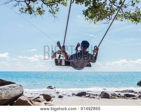 Young man swinging on tropical summer beach