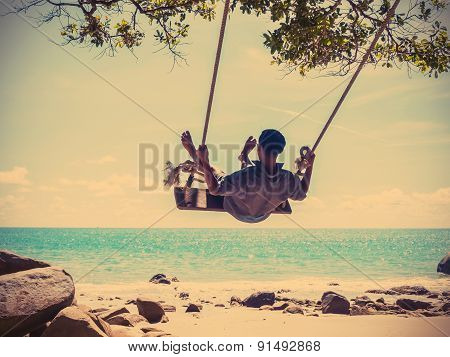 Young Man Swinging on beach