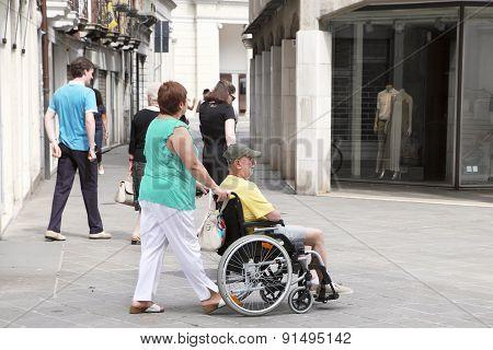 Venice, Mestre-june 29, 2014: Woman Pushing A Senior Man In A Wheelchair.  Venice, Mestre-june 29, 2
