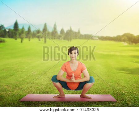 Pregnant Mother Doing Yoga At The Green Grass