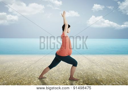 Pregnant Mother Doing Yoga At The Beach