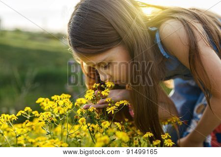 Little Girl Smelling A Yellow Flower