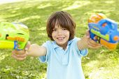 pic of pistols  - Young Boy Playing With Water Pistols In Park - JPG