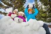 stock photo of snowball-fight  - Group of happy children hold snowballs  together standing behind the snow wall with fir forest on the background during winter day - JPG