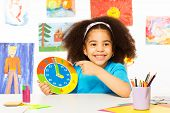 pic of child development  - African girl holding carton clock time while sitting at the table and wall behind with children drawings - JPG