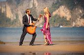 picture of guitarists  - dancing blonde girl in high heel shoes back - JPG