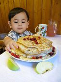 image of baby easter  - Baby boy sits by a table with Easter pancakes - JPG