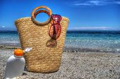 picture of suntanning  - straw bag and suntan lotion by the sea - JPG