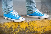 picture of snickers  - Brand new blue shoes and yellow concrete edge urban walking theme - JPG