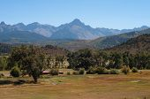 foto of colorado high country  - San Juan Mountains with green late summer meadows of a high country ranch are featured in this horizontal landscape photograph - JPG