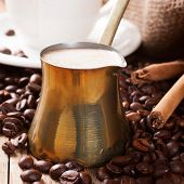 picture of cinnamon sticks  - Old coffee pot with coffee beans and cinnamon sticks on wooden rustic background - JPG