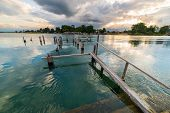 foto of jetties  - Old and damaged wooden jetty on lake Poso in central Sulawesi Indonesia with dramatic cloudscape at the horizon at sunset - JPG