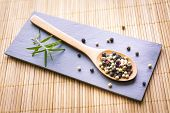 stock photo of condiment  - Pepper seeds in a wooden spoon and Rosemary herb for food condiment - JPG