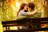 stock photo of illuminated  - Rear view of a Young couple in love sitting on a park bench illuminated by sunlight passionate look at each other in the moment before the kiss - JPG