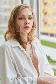 picture of blouse  - sad pretty woman in open white blouse near window - JPG