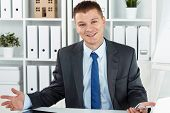 foto of mimicry  - Funny friendly smiling businessman in suit at office working desk making helpless gesture - JPG