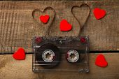 stock photo of magnetic tape  - Audio cassette with magnetic tape in shape of hearts on wooden background - JPG