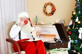pic of letters to santa claus  - Santa Claus sitting with children letters in comfortable chair near fireplace at home - JPG
