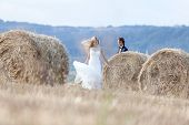 foto of hay bale  - Young married couple playing like kids running between hay bales. ** Note: Shallow depth of field - JPG