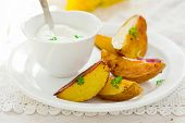 image of baked potato  - Segments of baked potato and sauce on a white plate - JPG