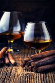 foto of cigar  - quality cigars and cognac on an old wooden table - JPG