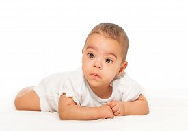 stock photo of babygro  - Serious looking African baby in white bodysuit on the white background - JPG