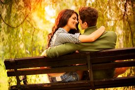 picture of sitting a bench  - Rear view of a Young couple in love sitting on a park bench illuminated by sunlight passionate look at each other in the moment before the kiss - JPG