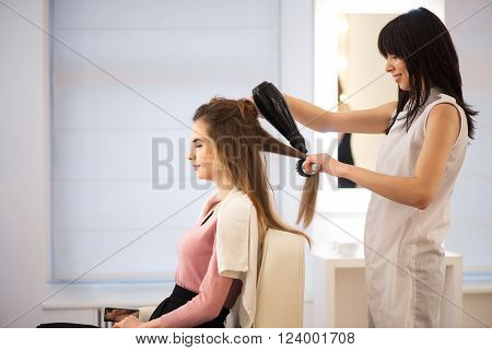 Best service Cheerful smiling professional hairdresser holding hairdryer   and drying hair of her client while working in the hairdressing salon