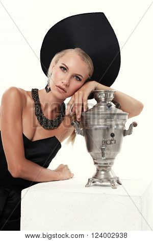 fashion studio photo of gorgeous woman with blond hair wears stylish national hat, posing with samovar