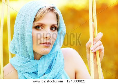 outdoor closeup portrait of a beautiful middle aged blonde woman in blue headscarf